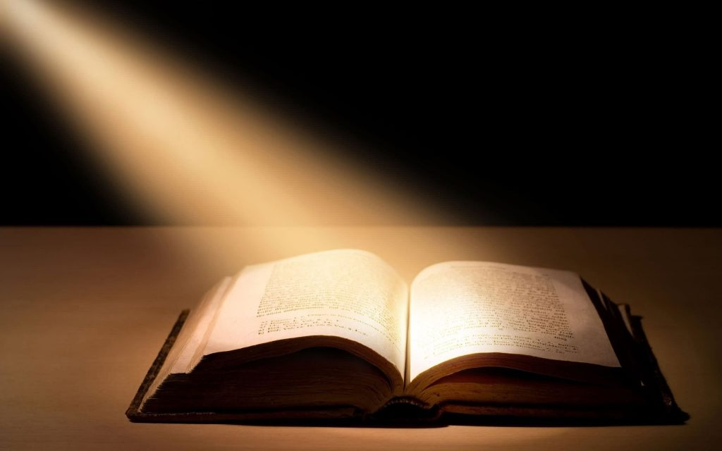Picture of an open bible on a table with light shining on it.